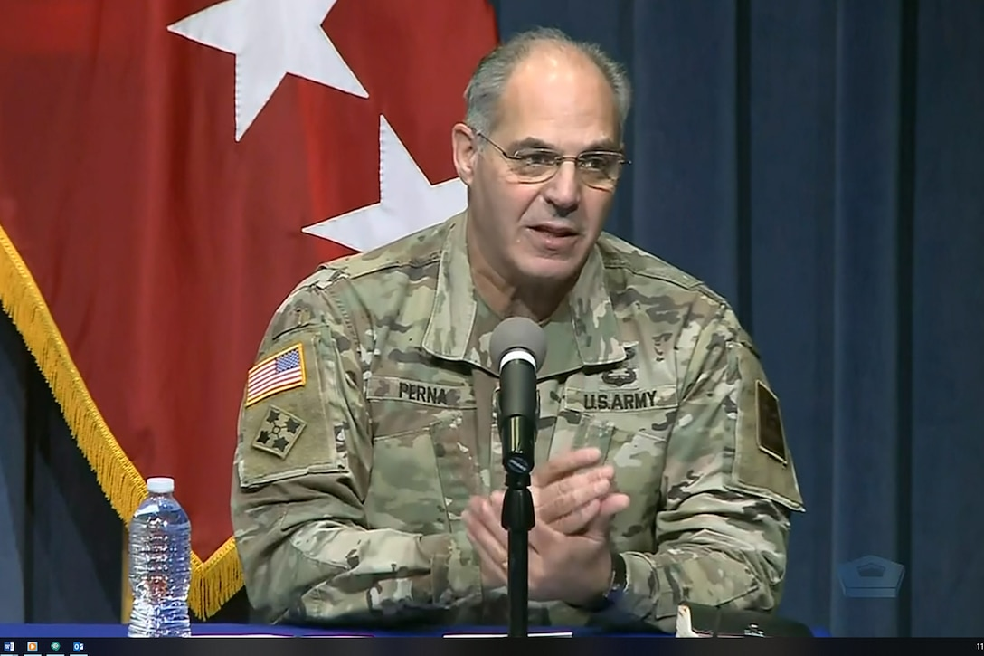 A man wearing a military uniform speaks into a microphone.