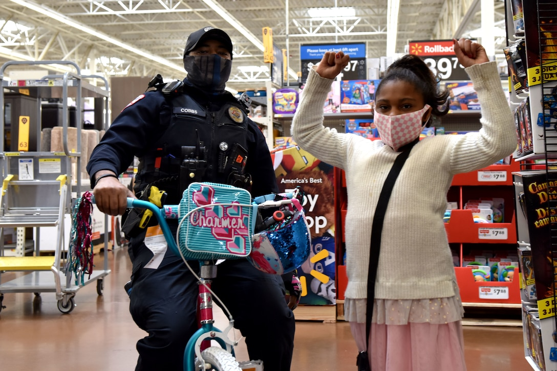 A San Angelo Police Officer tests out a bike that a participant in the 13th Annual Operation Blue Santa picked out as one of their gifts during the event in San Angelo, Texas, Dec. 12, 2020. Any child that picked out a bike also had to select a helmet for when they ride. (U.S. Air Force photo by Staff Sgt. Seraiah Wolf)