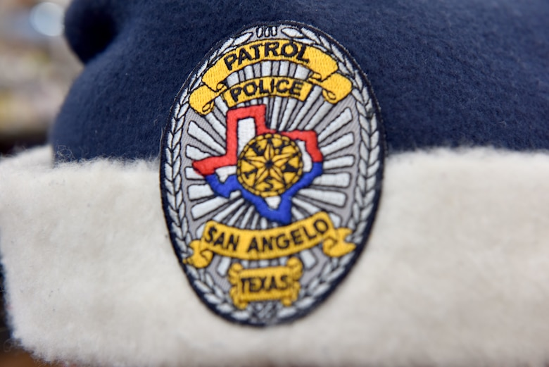 A police officer participating in the 13th Annual Operation Blue Santa shows off his blue Santa hat complete with a San Angelo police badge in San Angelo, Texas, Dec. 12, 2020. This year, many children safely participated in the event with COVID-19 restrictions. (U.S. Air Force photo by Staff Sgt. Seraiah Wolf)