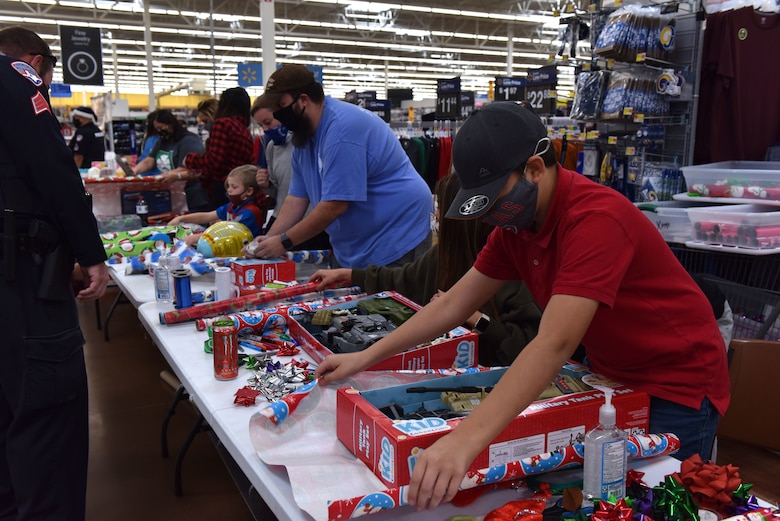Volunteers wrap gifts that participants of the 13th Annual Operation Blue Santa picked during the event in San Angelo, Texas, Dec. 12, 2020. Family members of the police officers helped participants pick out gifts, wrap presents or provide refreshments. (U.S. Air Force photo by Staff Sgt. Seraiah Wolf)