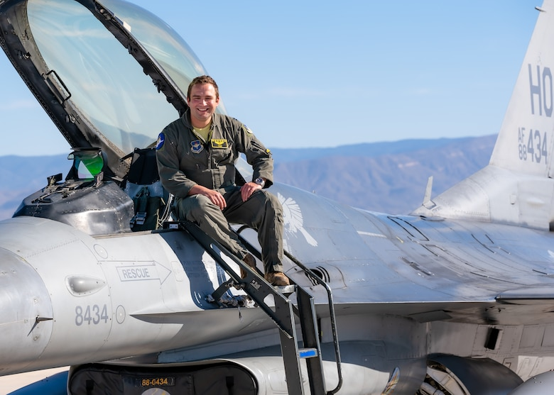 A plot in a green flight suit sits on top of a silver F-16 Viper aircraft in front of a blue sky.
