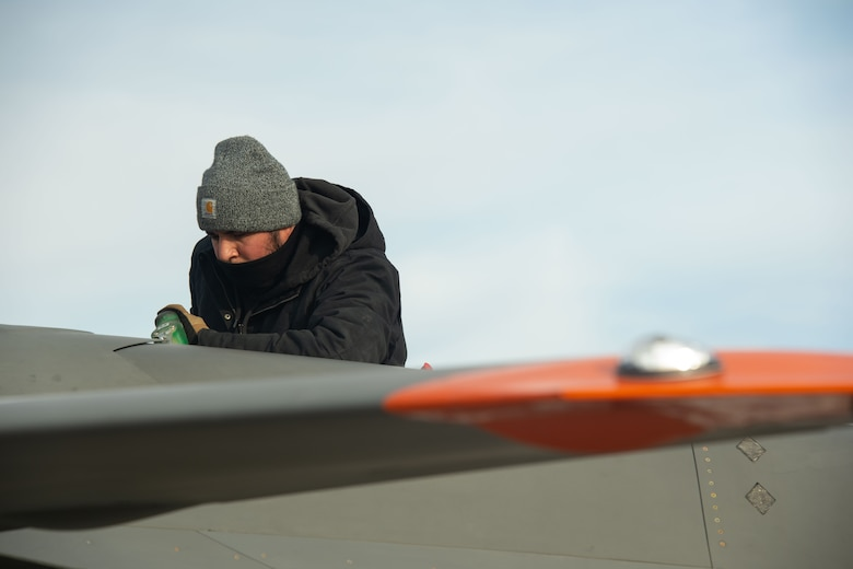 An XQ-58A Valkyrie maintainer pours fuel into the aircraft on a launchpad at the U.S. Army Yuma Proving Ground, Ariz., Dec. 9, 2020. More than 50 team members came together to make the historic flight a safe event. The joint effort included a Marine Corps F-35B variant, an Air Force F-22 Raptor, and an Air Force F-35A variant. The Air Force F-22 and F-35A aircraft flew with the attritableONE platform for the first time.