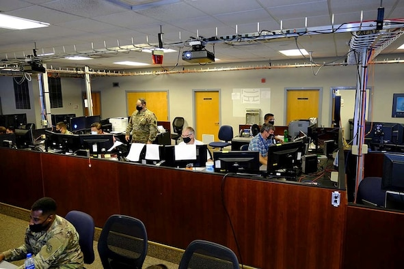 Photo of U.S. Air Force Airmen, civilians and contractors sitting at computers.