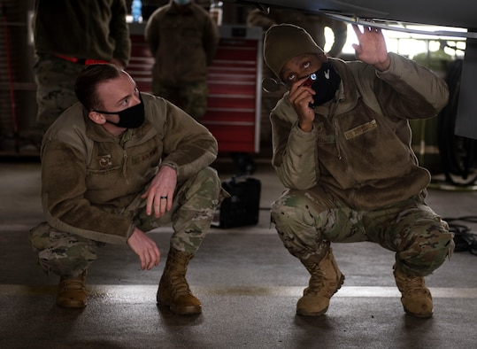 U.S. Air Force Staff Sgt. Joseph Livingston, 52nd Maintenance Group maintenance training instructor, left, and Tech Sgt. Jeremy Mayfield, 52nd Maintenance Squadron engine technician, conduct a pre-flight inspection on an F-16 Fighting Falcon, Dec. 9, 2020, at Spangdahlem Air Base, Germany. The Agile Combat Employment course allows Airmen to become certified in other career field capabilities, giving them the opportunity to become multifunctional and versatile whenever necessary. (U.S. Air Force photo by Senior Airman Melody W. Howley)