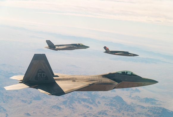 A U.S. Air Force F-22 Raptor and F-35A Lightning II fly in formation with the XQ-58A Valkyrie low-cost unmanned aerial vehicle over the U.S. Army Yuma Proving Ground testing range, Ariz., during a series of tests Dec. 9, 2020. This integrated test follows a series of gatewayONE ground tests that began during the inaugural Department of the Air Force on-ramp last year in December.