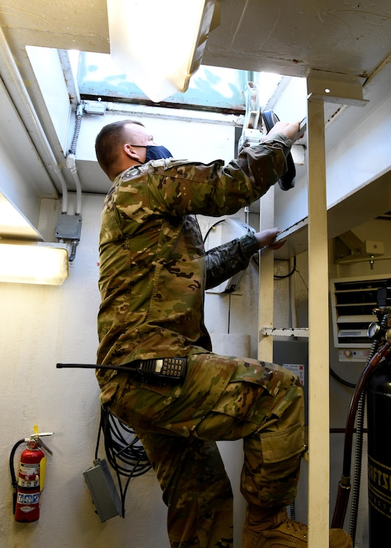 Tech. Sgt. Michael Reniewicz, 104th Fighter Wing power production shop leader, climbs out of a room containing arresting cables after performing routine maintenance December 10, 2020 at Barnes Air National Guard Base. (U.S. Air National Guard Photo by Airman 1st Class Camille Lienau