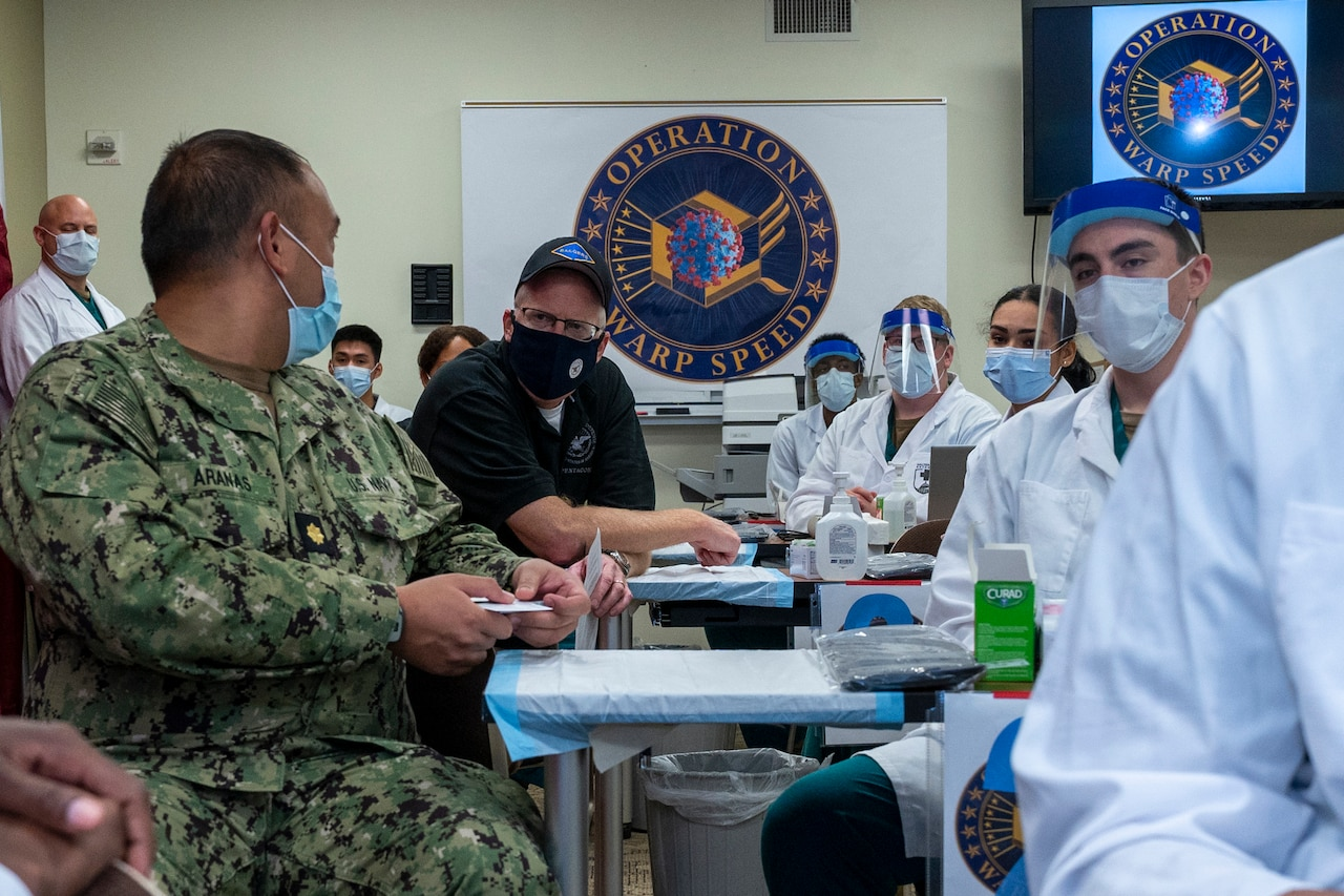 Two men speak to each other while sitting in a room full of people in medical uniforms.