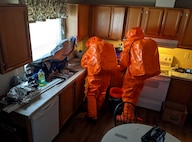 Sgt Matt Giddens and Staff Sgt. Dustin Foreman inspects a biological agent in the kitchen of an abandoned house