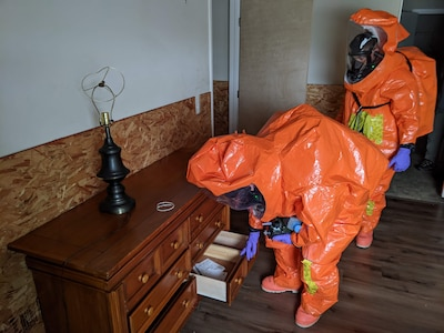 Sgt. Matt Giddens opens a dresser to discover whether it is contaminated as Staff Sgt. Dustin Foreman observes