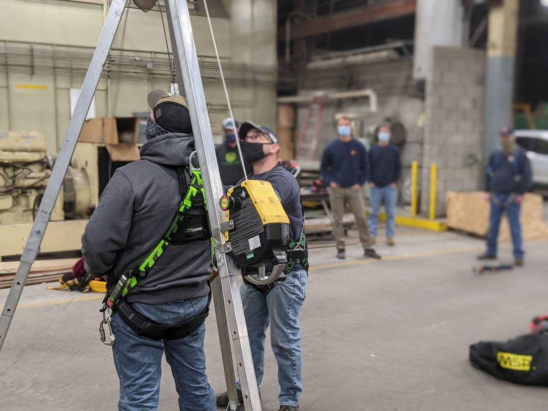 Students practice using a self-retractable lifeline and retrieval winch on a fall protection tripod.