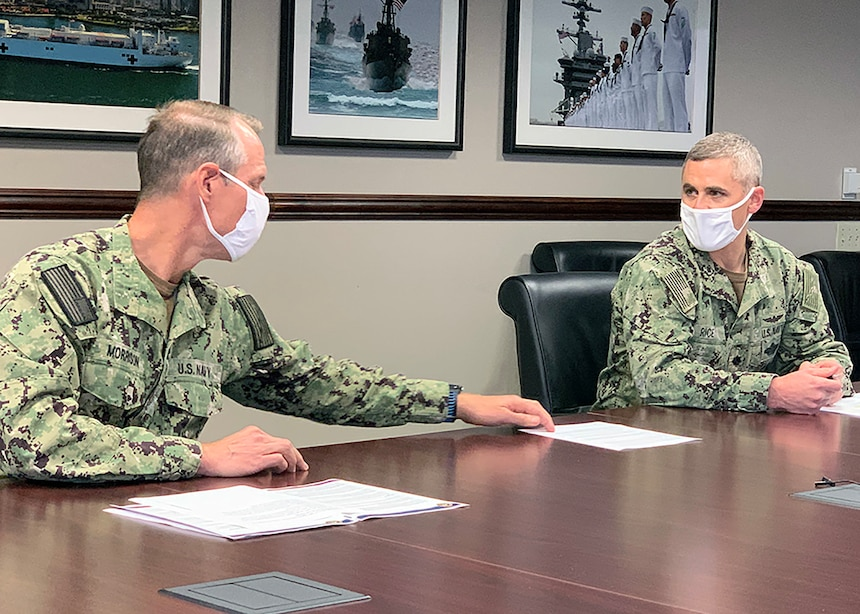 Capt. Devin Morrison, acting commanding officer of Naval Medical Center San Diego (NMCSD) and Cmdr. Jason Rice, director for public health and public health emergency officer (PHEO), compare notes ahead of the media roundtable teleconference held at NMCSD's conference room, Dec. 14.