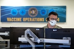 """Male wearing a face mask and headset sits in front of two computer screens with a sign  """"vaccine operations"""" behind him."""