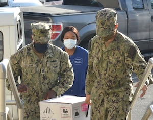 Sailors carry a container with COVID-19 vaccine at Naval Hospital Jacksonville.