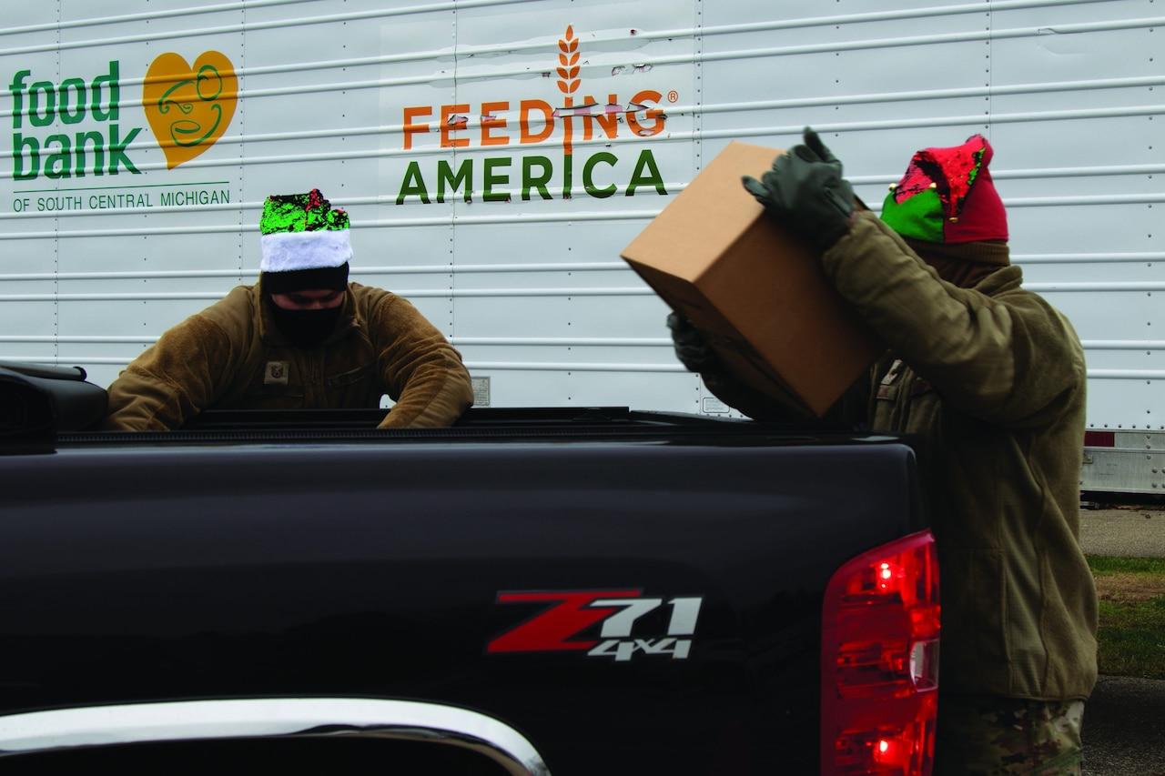 Two airmen help distribute food.