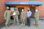 NSWC Indian Head Division Commanding Officer Capt. Scott Kraft presents EXU-1 Commanding Officer Cmdr. Edgar Britt with the Navy Unit Commendation, Dec. 15, at EXU-1's headquarters aboard Naval Support Facility Indian Head. Also pictured are Command Master Chief Jose Bryant (center), EXU-1's Civilian Director Alan Tompkins (center-right), and EXU-1's Executive Officer Lt. Cmdr. Jon Maurus (right). (U.S. Navy photo by Matt Poynor)