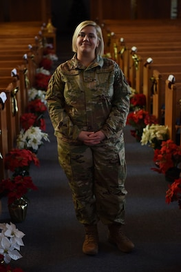 Airman Sara Boucher stands inside of the chapel between the pews, posing for a photo. Flowers line the floor behind her.