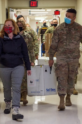 Jessica Benson, Oklahoma State Department of Health, leads Oklahoma National Guardsmen carrying boxes containing COVID-19 vaccinations to vehicles the Guard members will use to transport the vaccines to sites across the state, Dec. 15, 2020.  These are the first two boxes of vaccines to be distributed from one of five centralized hubs supporting 11 satellite locations across Oklahoma. The Guardsmen will be using Oklahoma State Department of Health vehicles to transport the vaccines to the satellite locations with an escort from the Oklahoma Highway Patrol. (Oklahoma National Guard photo by Anthony Jones)