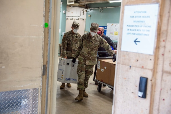 Spc. Martin Gamarra (left) and Airman 1st Class Andreas Owen (right) carry a box containing COVID-19 vaccinations after making their first delivery at a hospital in Oklahoma City, Dec. 15, 2020.  Gamarra and Owen are part of a larger team of Guardsmen who are delivering vaccines from from one of five centralized hubs supporting 11 satellite locations across Oklahoma. The Guardsmen will be using Oklahoma State Department of Health vehicles to transport the vaccines to the satellite locations with an escort from the Oklahoma Highway Patrol. (Oklahoma National Guard photo by Anthony Jones)