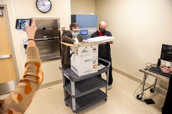 Shane Edmonson, executive director of pharmacy services, unseals the first shipment of COVID-19 vaccines delivered by Oklahoma National Guardsmen at the Mercy Hospital in Northwest Oklahoma City, Dec. 15, 2020.  The vaccines were delivered by Spc. Martin Gamarra and Airman 1st Class Andreas Owens. Gamarra and Owen are part of a larger team of Guardsmen who are delivering vaccines from from one of five centralized hubs supporting 11 satellite locations across Oklahoma. The Guardsmen will be using Oklahoma State Department of Health vehicles to transport the vaccines to the satellite locations with an escort from the Oklahoma Highway Patrol. (Oklahoma National Guard photo by Anthony Jones)