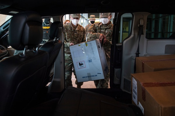 Spc. Martin Gamarra (right) and Airman 1st Class Andreas Owens (left) load a box containing COVID-19 vaccinations into  the vehicles the Guard members will use to transport the vaccines to sites across the state, Dec. 15, 2020.  On December 15, Guardsmen are transporting the first two boxes of vaccines to be distributed from one of five centralized hubs supporting 11 satellite locations across Oklahoma. The Guardsmen will be using Oklahoma State Department of Health vehicles to transport the vaccines to the satellite locations with an escort from the Oklahoma Highway Patrol. (Oklahoma National Guard photo by Anthony Jones)