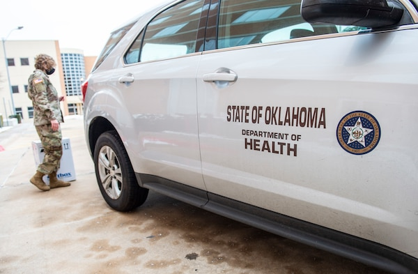 Oklahoma National Guardsmen prepare to load boxes of COVID-19 vaccinations into vehicles the Guard members will use to transport the vaccines to sites across the state, Dec. 15, 2020.  These are the first two boxes of vaccines to be distributed from one of five centralized hubs supporting 11 satellite locations across Oklahoma. The Guardsmen will be using Oklahoma State Department of Health vehicles to transport the vaccines to the satellite locations with an escort from the Oklahoma Highway Patrol. (Oklahoma National Guard photo by Anthony Jones)