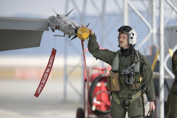 U.S. Marine Corps Maj. Elliott Snelgrove, an F/A-18 Hornet pilot with Marine Fighter attack Squadron (VMFA) 312 inspects an F/A-18D Hornet at Marine Corps Air Station Iwakuni, Japan, Dec 4, 2020. Marines with VMFA-312 provided close air support to Marines with 3rd Marine Division during training at Combined Arms Training Center (CATC) Camp Fuji. CATC Camp Fuji is a Marine Corps Installations Pacific Facility dedicated to modernized live, virtual, and constructive combined arms training. CATC Camp Fuji provides premier support for the accomplishment of air, ground, and amphibious training for the Marine Corps, joint U.S. forces, and our allies. (U.S. Marine Corps photo by Lance Cpl. Tyler Harmon)