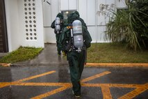 U.S. Marines with Chemical; Biological; Radiological; and Nuclear defense; 1st Marine Aircraft Wing; approach a building during hazardous environment training at Camp Lester; Okinawa; Japan; Dec. 9; 2020. This training event was conducted to strengthen the unit's proficiency and readiness when operating in hazardous environments. (U.S. Marine Corps photo by Cpl. Ethan M. LeBlanc)
