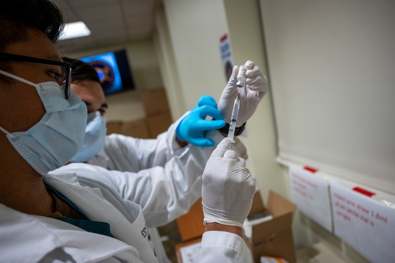 A hospital worker uses a syringe to draw fluid from a small bottle.