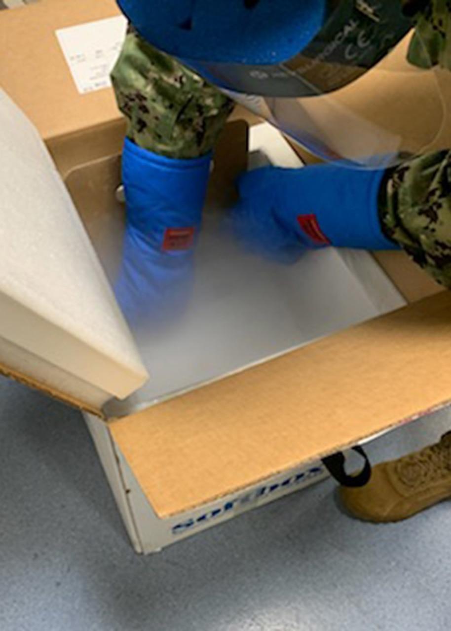 A sailor handles a box of vaccines.