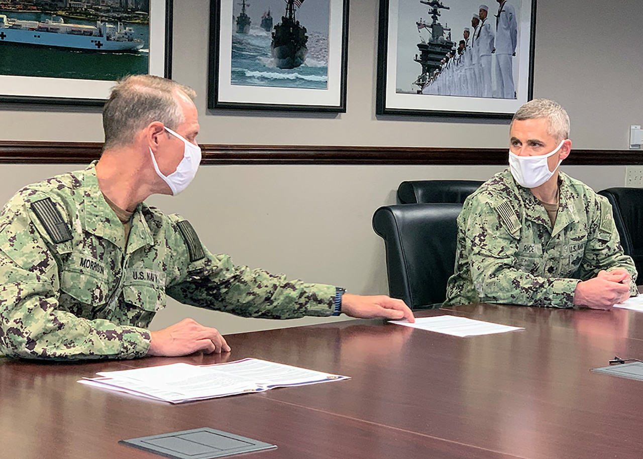 Two military leaders wearing face masks sit at a conference table.