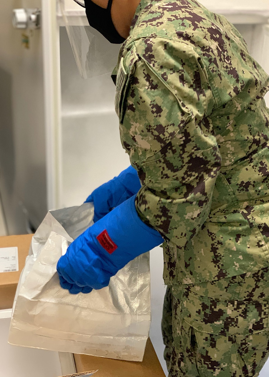 A sailor prepares to handle a box of vaccines.
