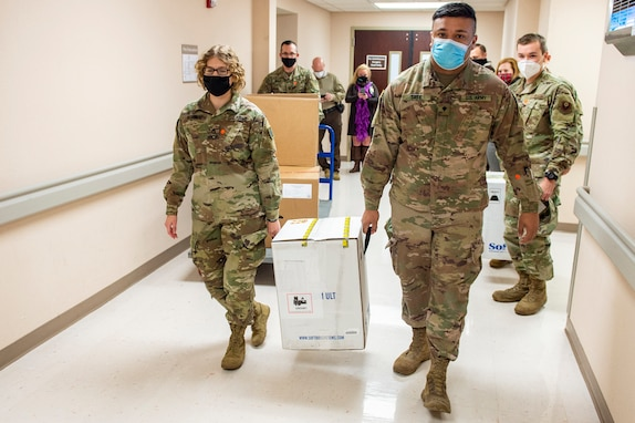 Oklahoma National Guard Cpl. Danielle O'Connor and Spc. Ryan Tate, right, carry an ultra-cold box containing COVID-19 vaccinations to vehicles to transport the vaccines to sites across the state, Dec. 15, 2020. These are the first vaccines to be distributed in Oklahoma from one of five centralized hubs supporting 11 satellite locations. (U.S. Army National Guard photo by Army Sgt. Anthony Jones)