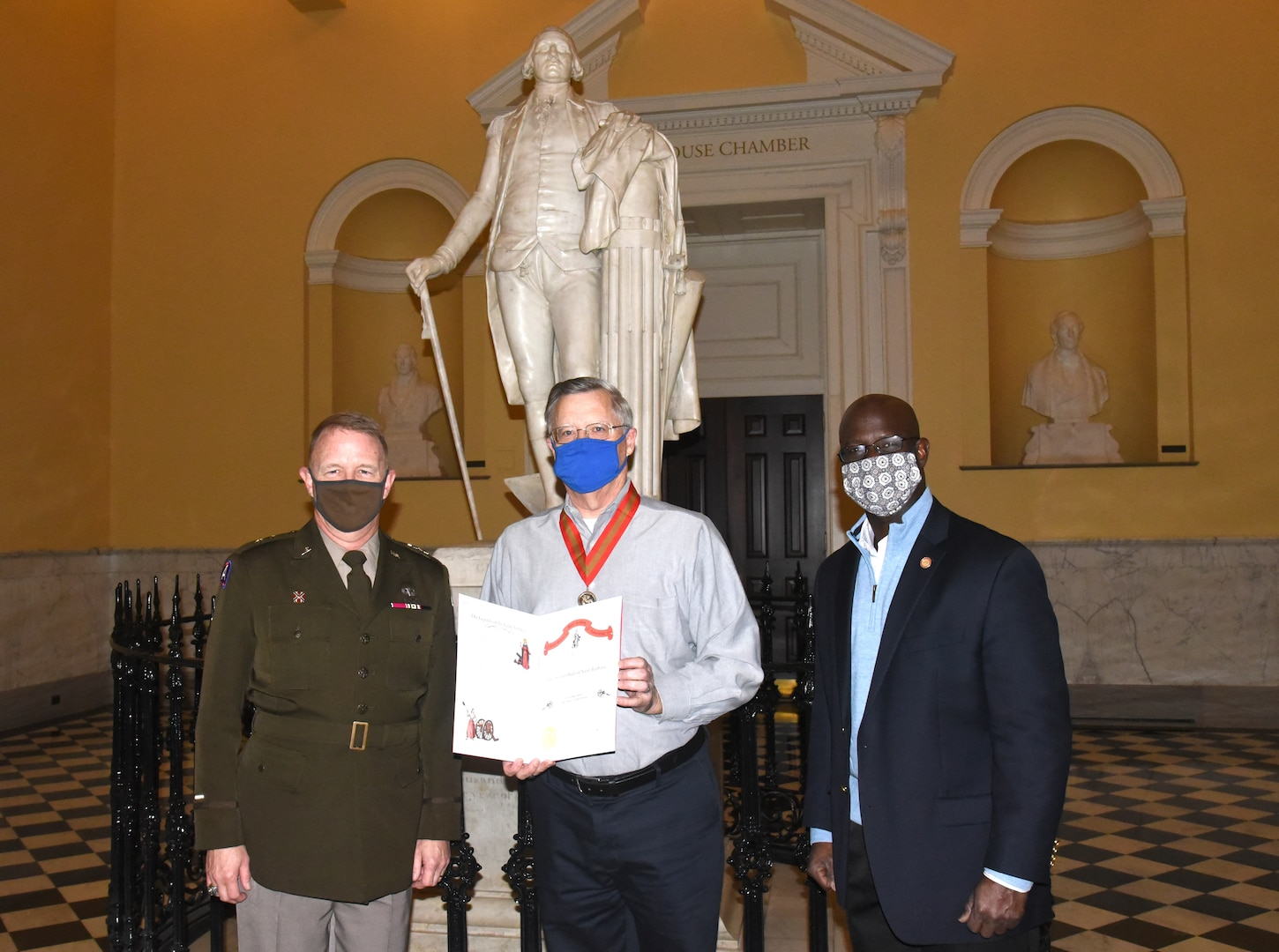 Maj. Gen. Timothy P. Williams, the Adjutant General of Virginia, presents the Ancient Order of St. Barbara to retired Col. Mike Coleman during a ceremony at the Capitol of Virginia Dec. 14, 2020, in Richmond, Virginia.