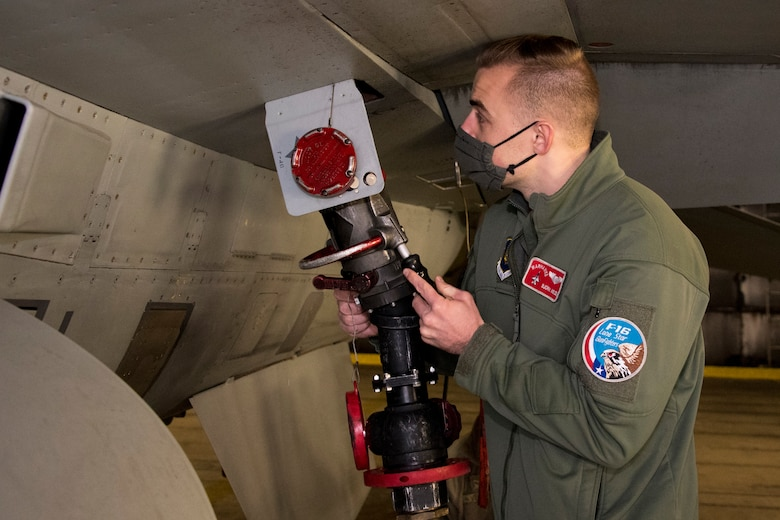 U.S. Air Force First Lt. Bjorn Nielsen, 480th Expeditionary Fighter Squadron pilot, inserts a fuel pump into an F-16 Fighting Falcon during an Agile Combat Employment training at Spangdahlem Air Base, Germany, Dec. 11, 2020. This training allows for the pilots to become more versatile, minimize aircraft downtime and increase mission effectiveness in a deployed environment. (U.S. Air Force photo by Senior Airman Chance D. Nardone)