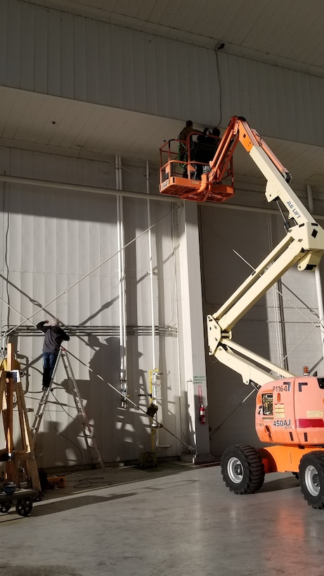 Photo shows two men in a lift drilling wires into the ceiling.