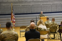 Lt. Col. Jeremy Stevenson stands behind podium and speaks to audience.