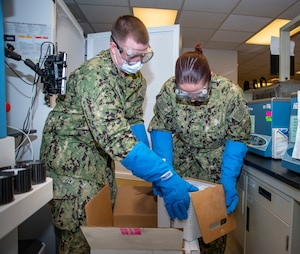 Hospital corpsman unload a shipment of COVID-19 vaccine into a freezer at Naval Medical Center Portsmouth.