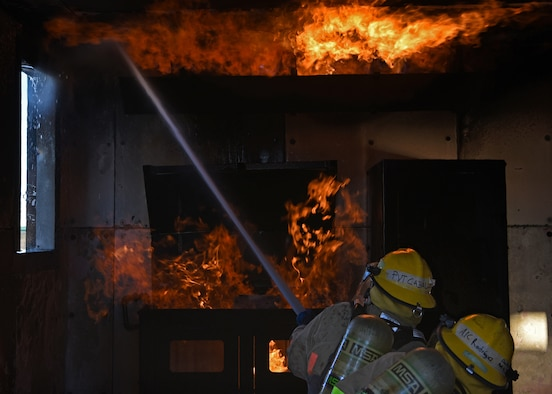 U.S. Army Pvt. Arias Caballero and Air Force Airman 1st Class Jorge Rodriquez-Aponte, 312th Training Squadron fire protection students, extinguish the burning room together during their grade level interior fire training exercise at the Louis F. Garland Department of Defense Fire Academy on Goodfellow Air Force Base, Texas, Dec. 10, 2020.  The students were assigned to three units which all had different roles to play during a structure fire. (U.S. Air Force Senior Airman Abbey Rieves)
