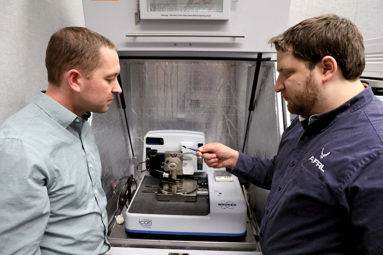 Dr. Nicholas Glavin, (left) research scientist at the Air Force Research Laboratory and David Moore, research scientist at UES, Inc. loading the sample into the analysis chamber. (U.S. Air Force photo/Spencer Deer)