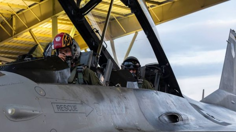 A photo of two people in the cockpit of an F-16 Fighting Falcon.
