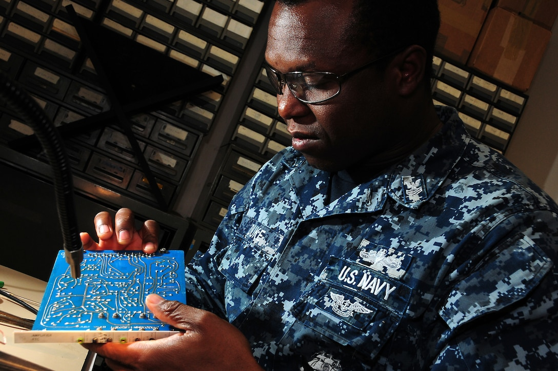 A man in a uniform inspects a circuit board.