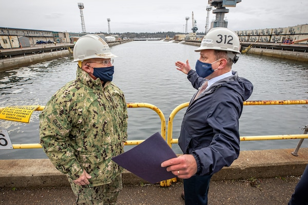 Chief of Naval Operations Adm. Mike Gilday discusses future Dry dock 6 seismic upgrades with Chris Hughes, Code 312, Carrier Program manager, Dec. 16, 2020, during Gilday's tour of Puget Sound Naval Shipyard & Intermediate Maintenance Facility in Bremerton, Washington. (PSNS & IMF photo by Scott Hansen)