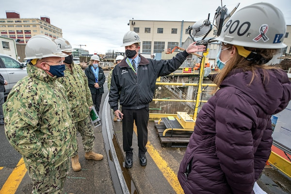 Chief of Naval Operations Adm. Mike Gilday is briefed by Sean Swansboro, Inactive Fleet, Reactor Compartment Disposal (RCD) and Recycling Program manager, and Amy O'Malia, Production Facilities and Plant Equipment manager, on Shipyard Infrastructure Optimization Program upgrades, and RCD disposal, Dec. 16, 2020, at Dry dock 3, during Gilday's tour of Puget Sound Naval Shipyard & Intermediate Maintenance Facility in Bremerton, Washington. (PSNS & IMF photo by Scott Hansen)