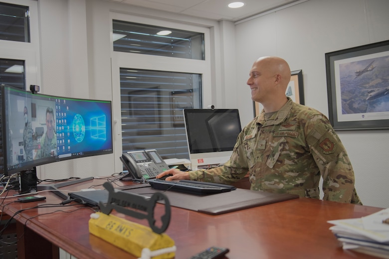 Commander standing at desk with computer.