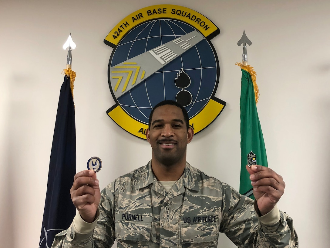 Airman holding two coins.