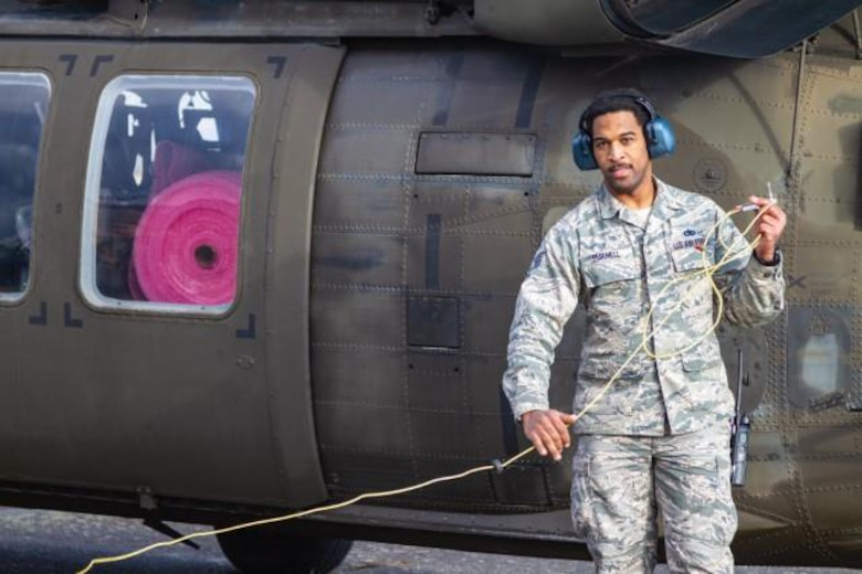 Airman standing in front of helicopter.
