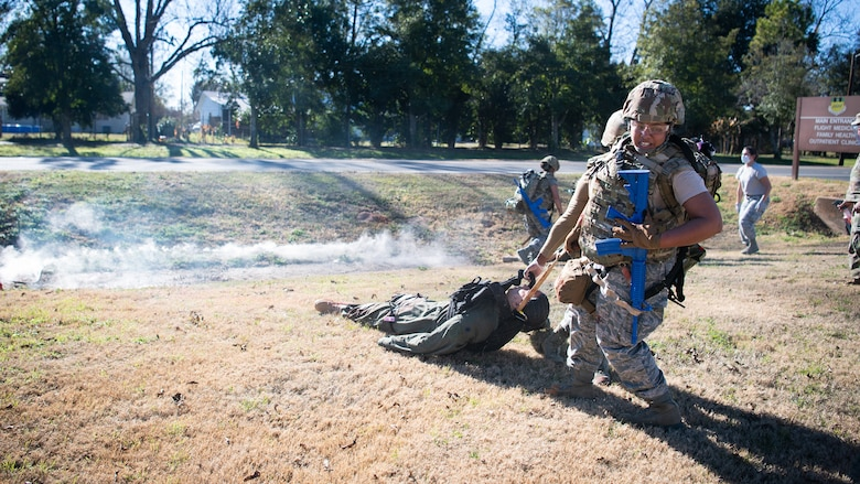 Staff Sgt. Jelisa Adams, 2nd Healthcare Operations Squadron medical technician, and Senior Airman Nikolas Swift, 2nd HCOS medical technician, drag a training dummy during a Tactical Combat Casualty Care (TCCC) field training exercise at Barksdale Air Force Base, La., Dec. 9, 2020.