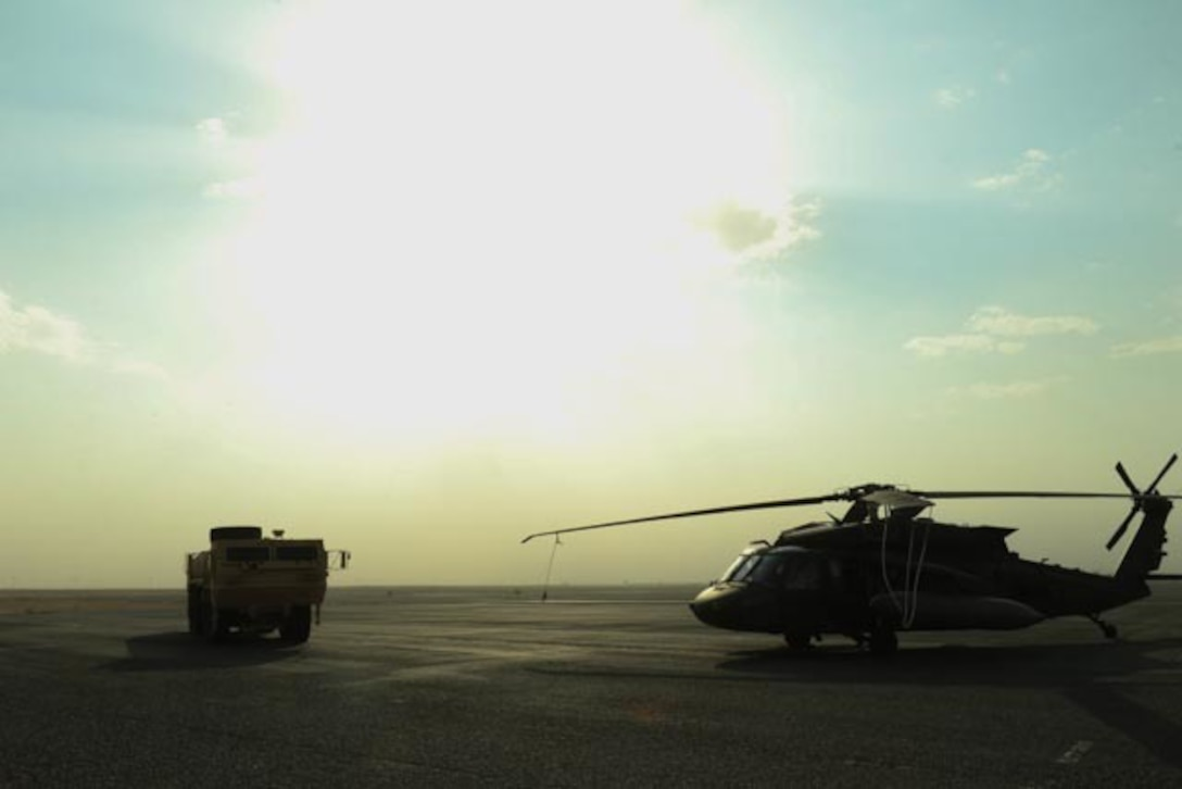 A helicopter and a vehicle sit on the desert floor.