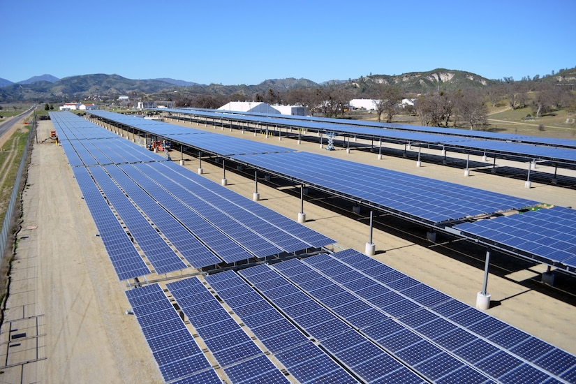 Rows of solar panels are lined up at a construction site.