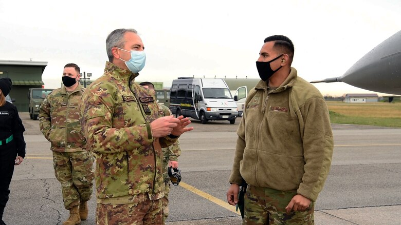 Tech. Sgt. Mario Osorno, 31st Aircraft Maintenance Squadron weapons load crew chief, right, speaks with an Italian air force member at Rivolto Air Base, Italy, Dec. 16, 2020. U.S. and Italian airmen spoke about the differences between the F-16 A and B models, which the Italians had experience with, and the C and D models, which are used by the 31st Fighter Wing today. (U.S. Air Force photo by Staff Sgt. Heidi Goodsell)